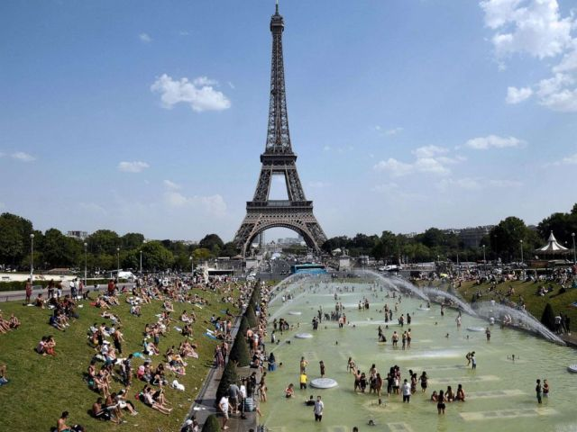 PHOTO: In this file photo taken on July 25, 2019, people cool off and sunbathe by the Trocadero Fountains next to the Eiffel Tower in Paris, as a new heatwave hits the French capital.