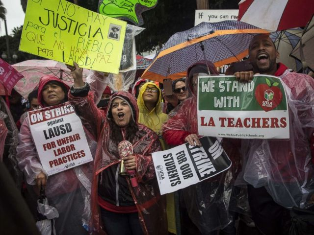 PHOTO: People gather in the downtown streets in the pouring rain during the United Teachers strike in Los Angeles on January 14, 2019 in Los Angeles.