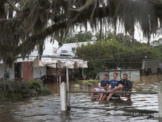 PHOTO: People sit in a swing surrounded by water from Lake Pontchartrain after the area flooded in the wake of Hurricane Barry on Saturday, July 13, 2019 in Mandeville, La.