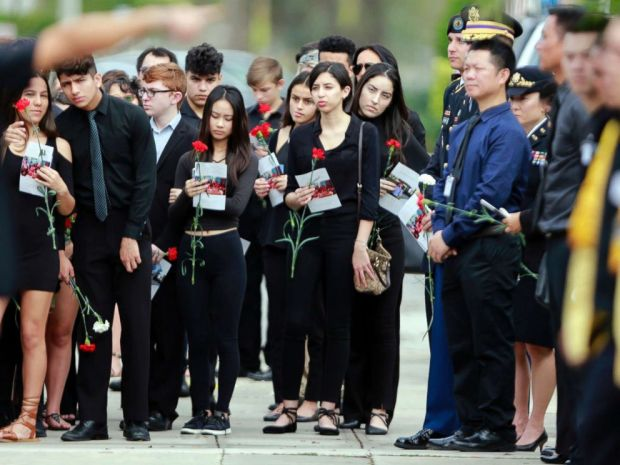 PHOTO: Mourners hold flowers during the funeral for Peter Wang at Kraeer Funeral Home in Parkland, Fla., on Feb. 20, 2018.