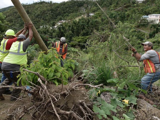 PHOTO: Public Works Sub-Director Ramon Mendez, wearing a hard hat at left, works with locals who are municipal workers, as they install a new post to return electricity to a home in the El Ortiz sector of Coamo, Puerto Rico, Jan. 31, 2018.