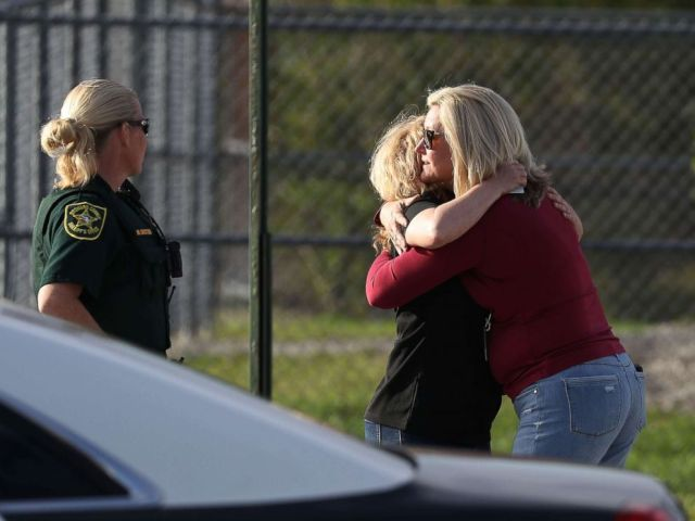 PHOTO: Assistant Principle Denise Reed (R) hugs a school employee as teachers and staff are allowed to return to the school for the first time since the mass shooting on campus on Feb. 23, 2018 in Parkland, Florida.