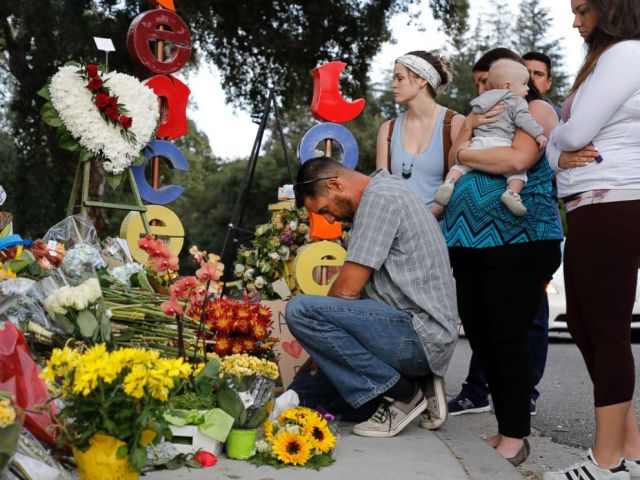 PHOTO: Jason Coffman, father of slain victim Cody Coffman, kneels at a memorial not far from where the Borderline Bar and Grill shooting happened in Thousand Oaks, Calif., Nov. 15, 2018.