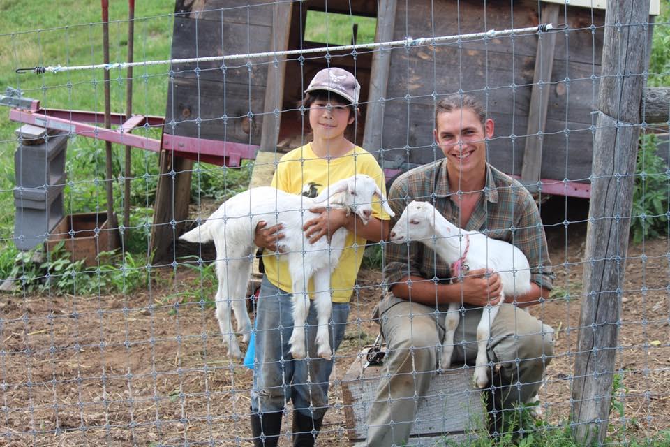 農場のスタッフと子ヤギを抱く鷹之介君(左)=アメリカ・マサチューセッツ州のライトロック農場