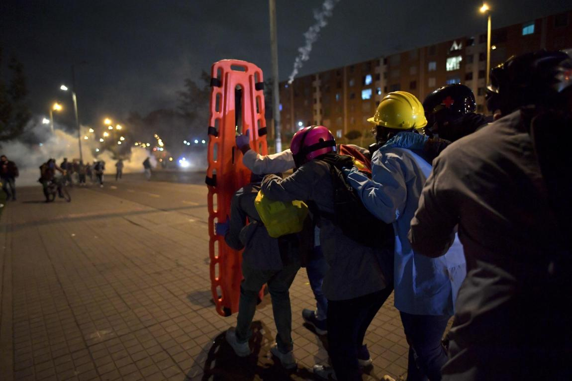 Volunteers wait using a stretcher as a shield to assist a protester injured during clashes with the Police in a protest against the government of Colombian President Iván Duque, at Portal de las Américas station, in Bogota, on May 26, 2021.