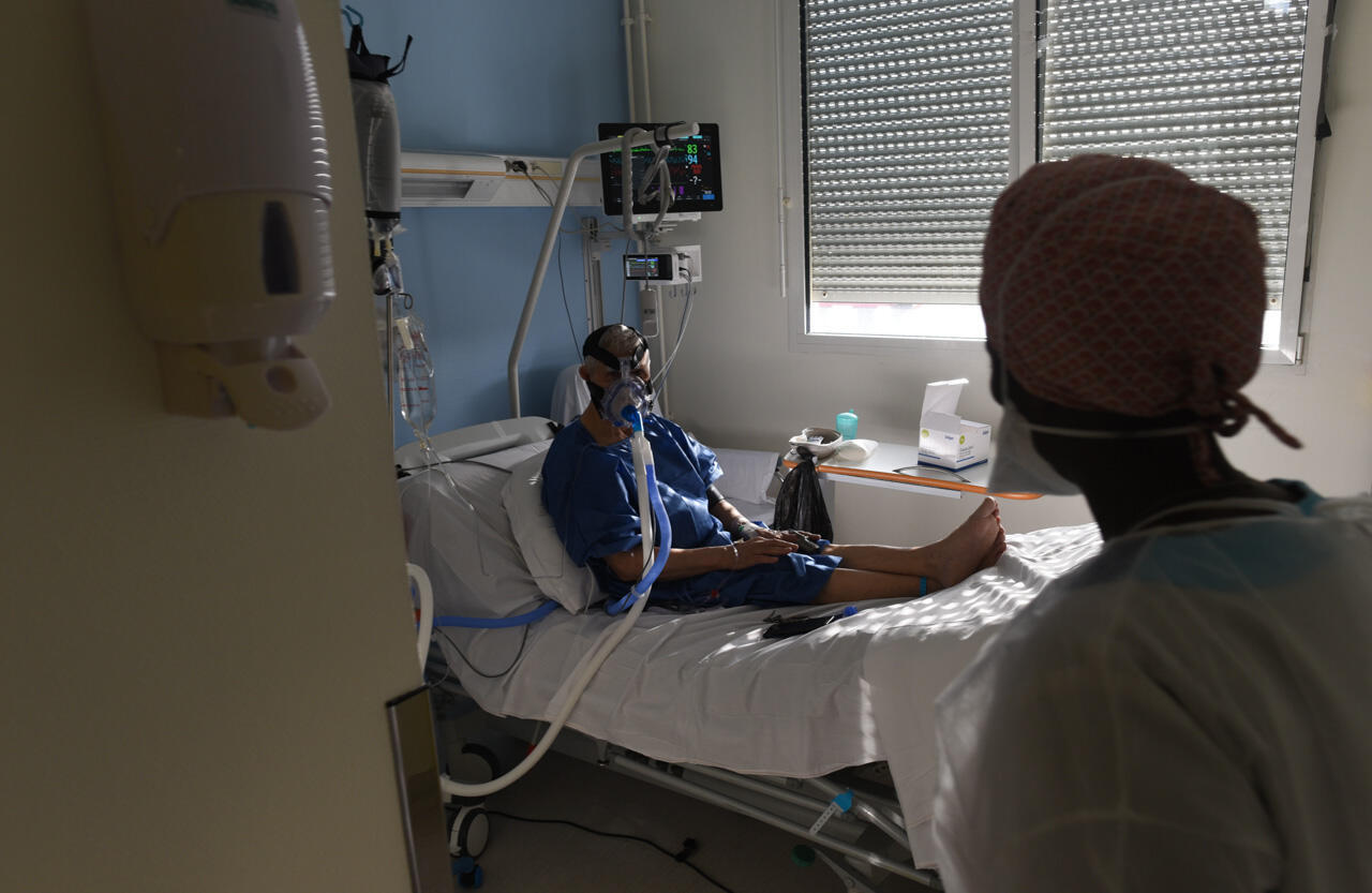 A patient breathes with the help of an oxygen mask, a non-invasive form of ventilation.