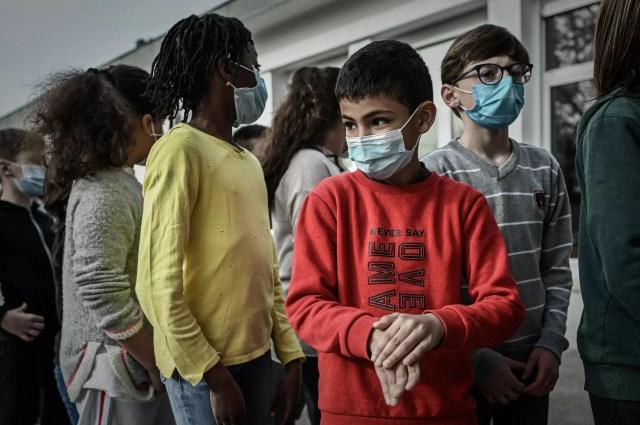Varios niños se limpian las manos con gel hidroalcohólico antes de que les tomen una muestra de saliva para una prueba de detección del coronavirus, el 25 de febrero de 2021 en una escuela de Eysines, a las afueras de la ciudad francesa de Burdeos