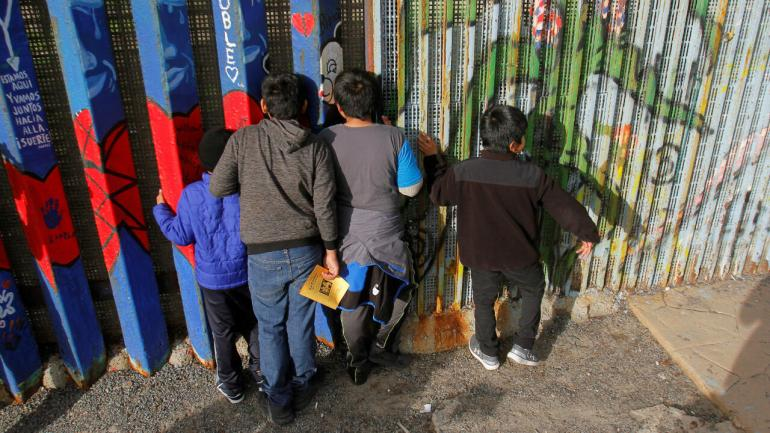 File-Central American migrant children look through the side of the border wall in Tijuana as they gather to celebrate the Christmas season in Tijuana, Mexico, on December 14, 2019.