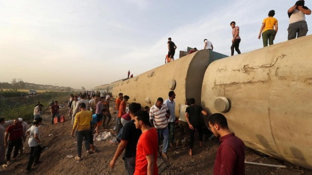 People gather at the site where train carriages derailed in Qalioubia province, north of Cairo, Egypt April 18, 2021.