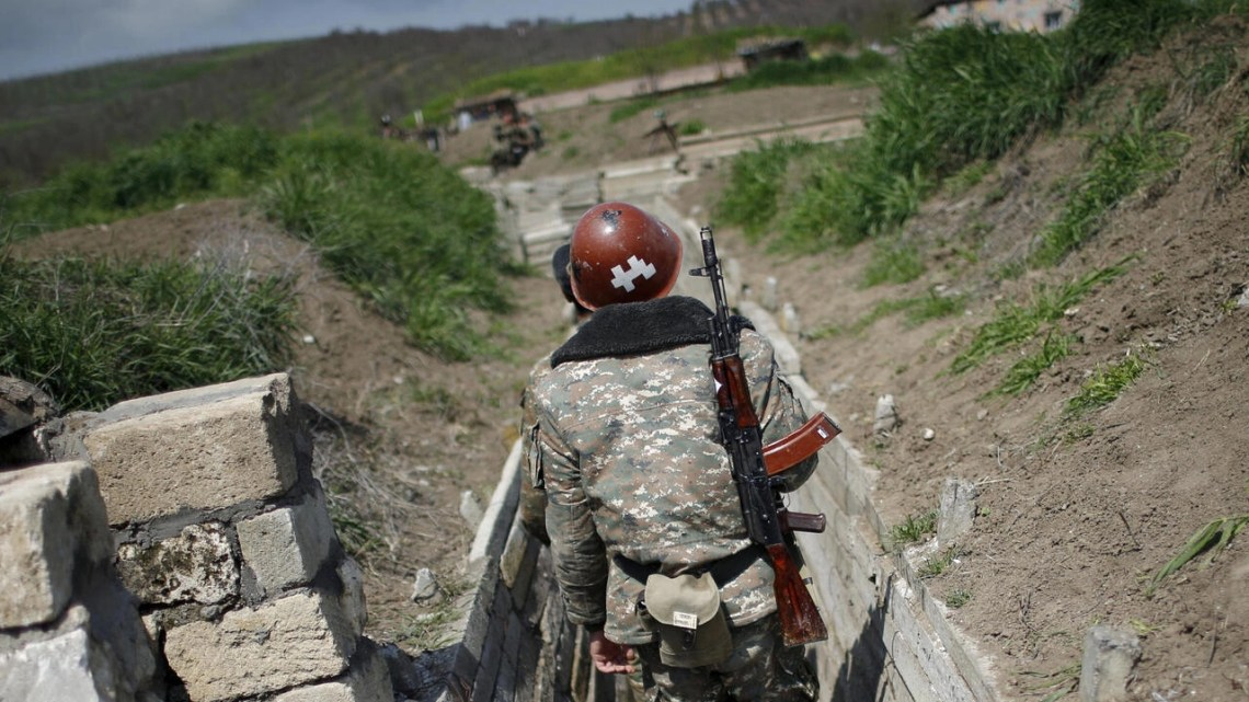 Ethnic Armenian soldiers walk in a trench at their position near the border of the Nagorno-Karabakh region on April 8, 2016