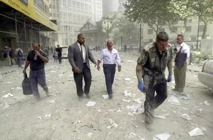 En esta foto de archivo tomada el 11 de septiembre de 2001, un oficial de policía (derecha) y otros caminan por calles cubiertas de escombros luego del colapso de las torres gemelas del World Trade Center en Nueva York.