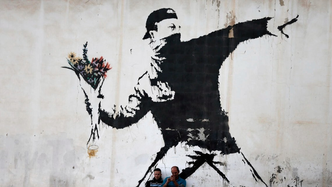 Two men sit in front of Banksy's 'Flower Thrower' mural painted on a wall of a petrol station in the West Bank town of Bethlehem