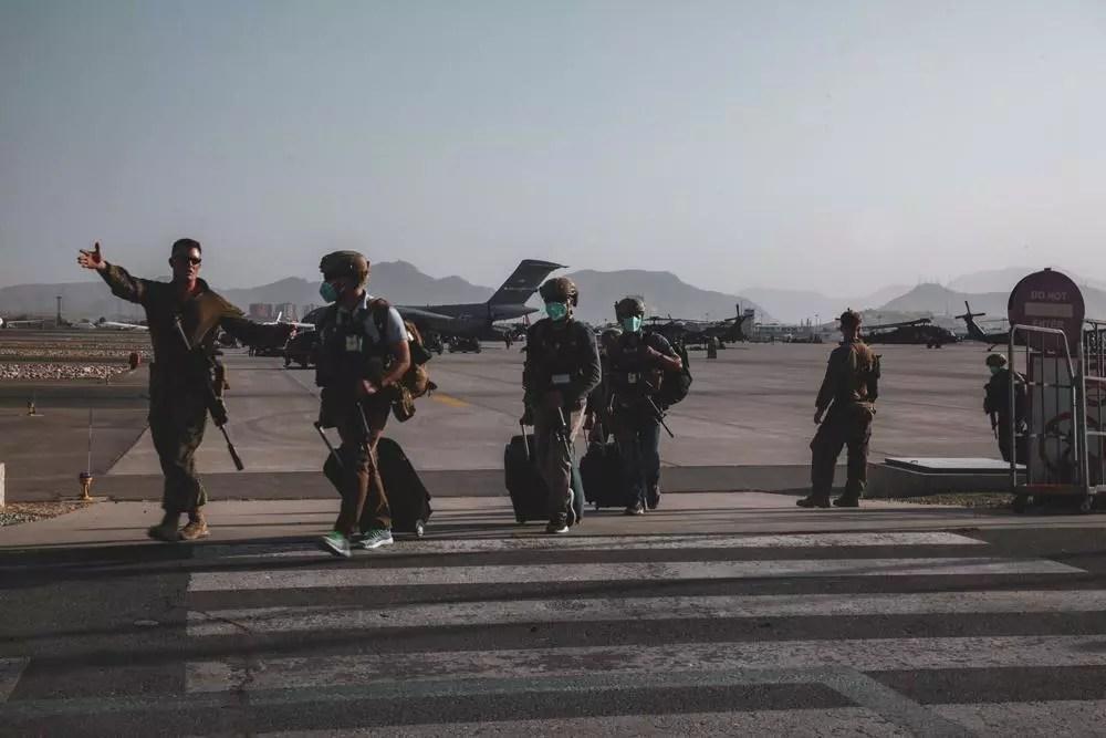 Un marine asignado a la 24ª Unidad Expedicionaria de Marines (MEU) escolta a personal del Departamento de Estado para ser procesado para su evacuación en el Aeropuerto Internacional Hamid Karzai, en Kabul, Afganistán, el domingo 15 de agosto de 2021.