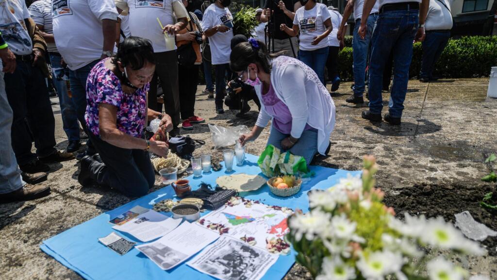 """La gente enciende velas y coloca flores junto a un """"anti-monumento"""" colocado por activistas para conmemorar el décimo aniversario del San Fernando en la Ciudad de México, el 22 de agosto de 2020."""
