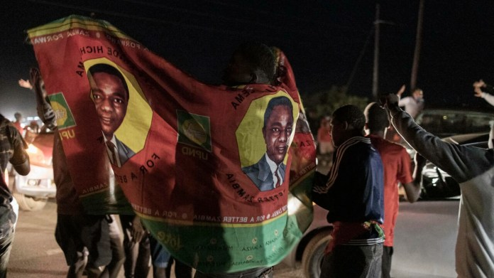A person wears a party flag as a long line of cars of supporters of Zambian presidential candidate for the opposition party United Party for National Development (UPND) Hakainde Hichilema parade in front of his residence celebrating in Lusaka on August 15, 2021.