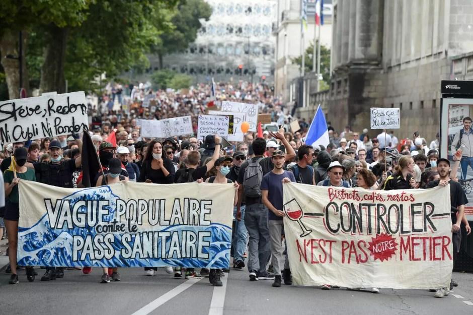 Los manifestantes sostienen pancartas durante una manifestación contra el pase de salud obligatorio Covid-19 para acceder a la mayor parte del espacio público, en Nantes, en el oeste de Francia, el 4 de septiembre de 2021.