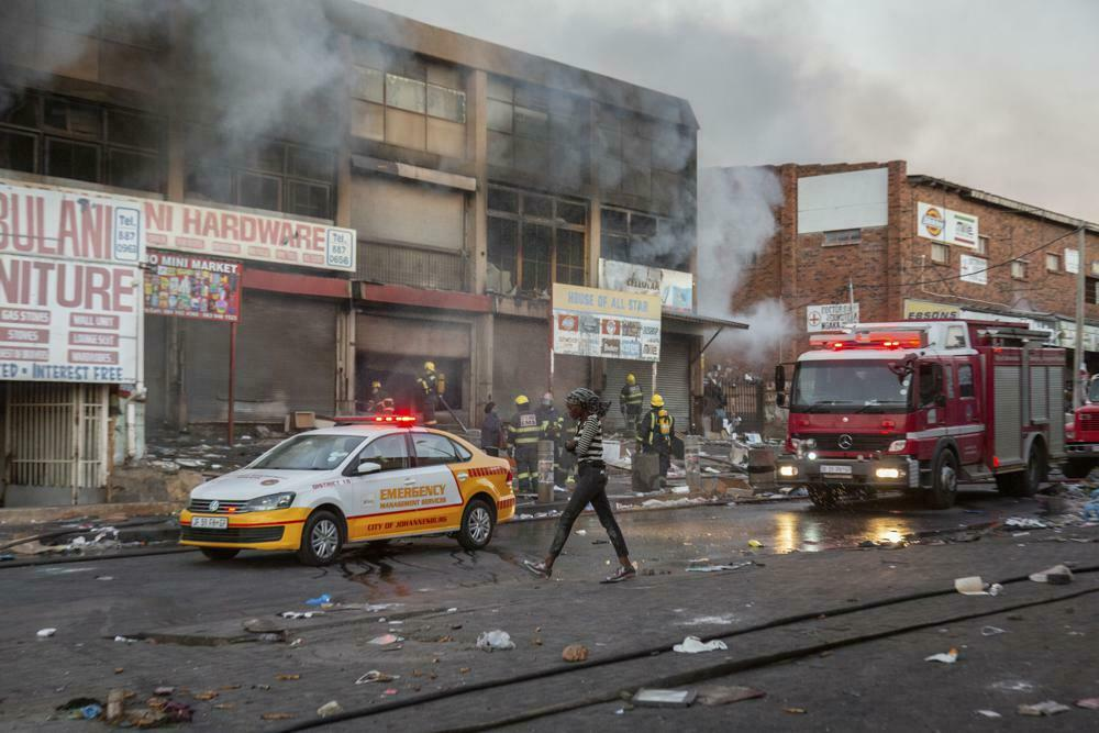 A woman walks past a fire truck as she puts out flames at a looted shop in Alexandra Township, Johannesburg, South Africa, on Monday, July 12, 2021.