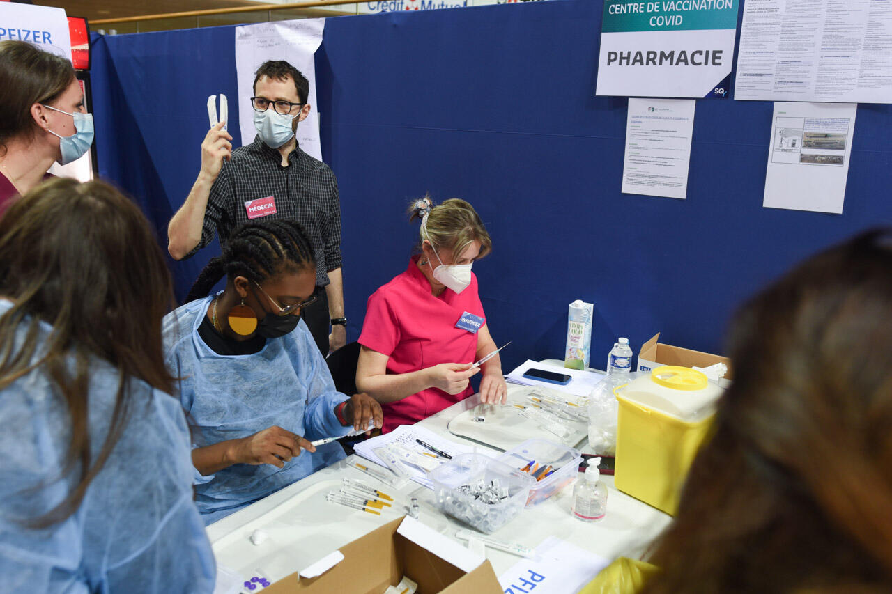 The pharmacy stall, where nurses prepare the syringes. It is the beating heart of the vaccinodrome, where healthcare workers file in non-stop to retrieve doses to inject.
