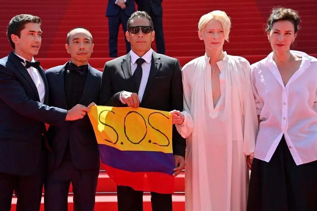 (de izquierda a derecha) el actor colombiano Juan Pablo Urrego, el director tailandés Apichatpong Weerasethakul, el actor colombiano Elkin Diaz, la actriz británica Tilda Swinton y la actriz francesa Jeanne Balibar, posan en la alfombra roja con la bandera de Colombia durante la edición 74 del Festival de Cannes, en Francia. 15 de julio de 2021.