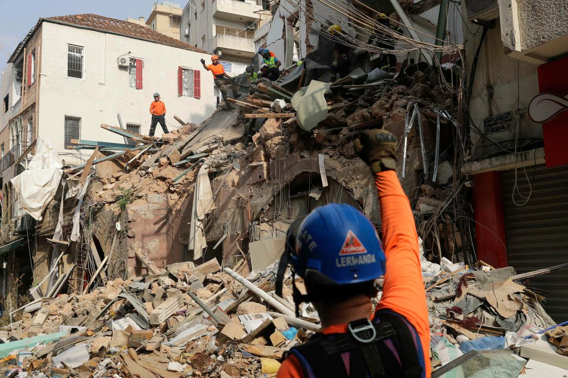 Rescue workers dig through the rubble of a badly damaged building in Lebanon's capital Beirut looking for possible survivors on September 3, 2020, a month after a mega-explosion at the port destroyed much of the city.