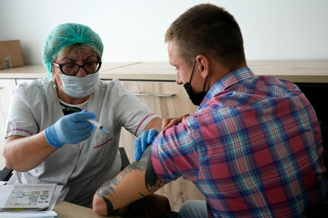 A medical worker prepares to administer an injection of Russia's Sputnik V coronavirus vaccine to an employee at Oleg Sirota's cheese factory in the village of Dubrovskoye, Russia, on July 15, 2021.