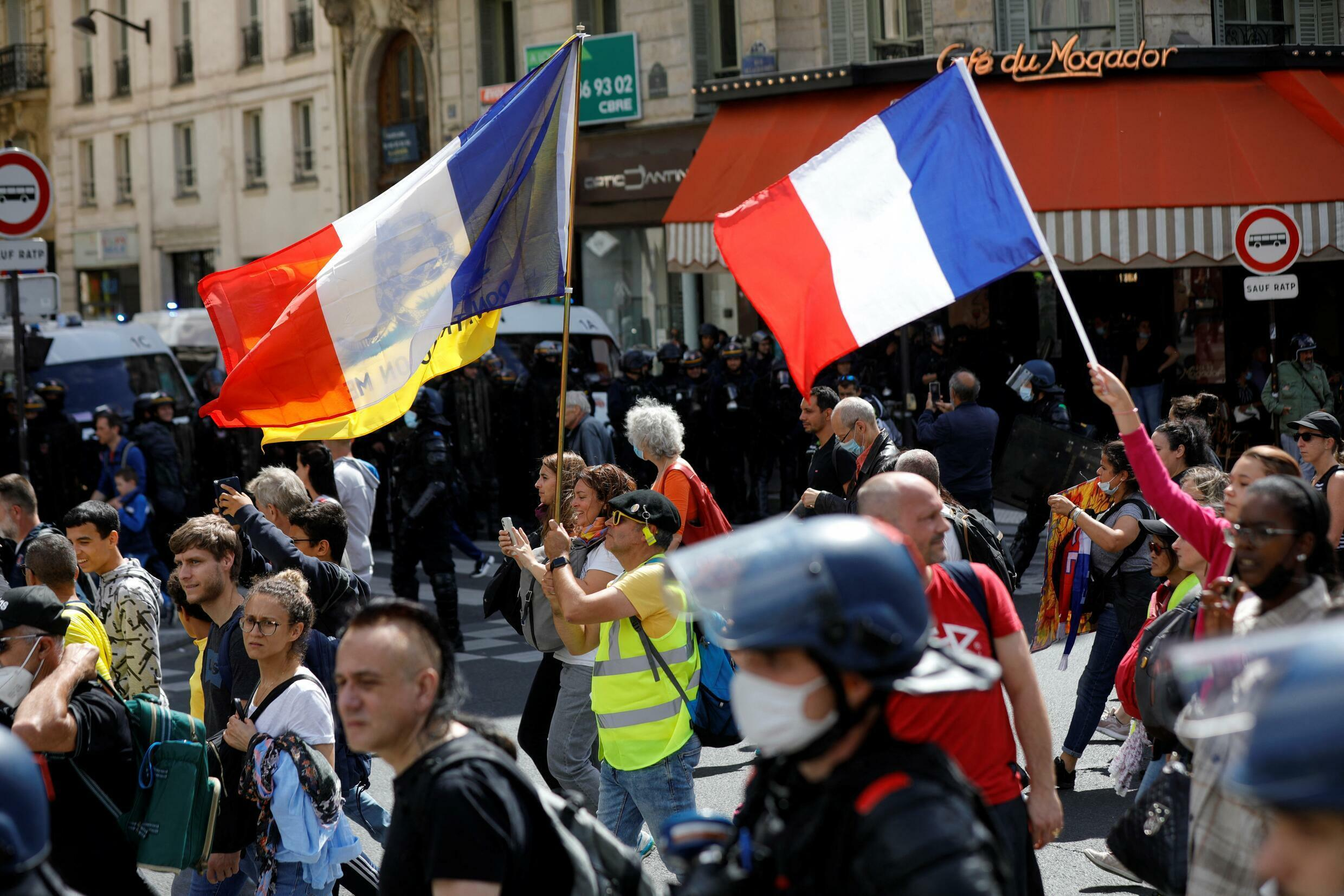 Protesters hold the French flag during a national day of protest against the Government's Covid-19 health pass, in Paris, France, on August 7, 2021.