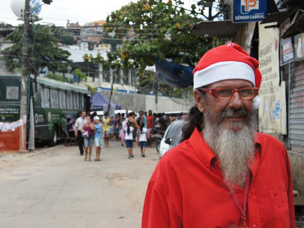 """O morador Paulo Alexandre da Costa, 68 anos, alegrou o começo da tarde desta quinta-feira (2), na comunidade da Grota, no Conjunto de Favelas do Alemão. Vestido com roupas vermelhas e o típico chapéu de Papai Noel, Costa circulou pelas pessoas dando a característica risada do """"bom velhinho"""": ho! ho! ho!  """"Minha vontade era de trazer um pouco de alegria para os olhos das crianças da região, que só têm visto desgraça e violência. Quero que elas lembrem do espírito de Natal e coloquem o sorriso de volta no rosto"""", disse o Papai Noel."""