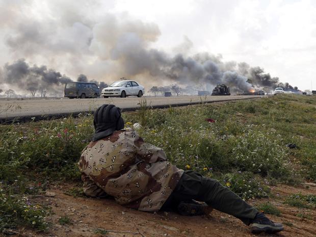 Rebelde líbio observa veículos das forças pró-Kadhafi queimando após ataque aéreo da coalizão, na estrada entre Benghazi e Ajdabiyah, neste domingo (20). (Foto: Reuters)