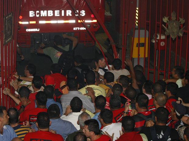 Bombeiros se espremem para entrar no quartel Central do Corpo de Bombeiros (Foto: André Teixeira/ Ag. O Globo)