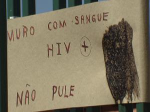 Cartaz colado em grade de casa do condomínio RK, em Sobradinho, avisa sobre seringas que teriam sangue com HIV (Foto: Reprodução/TV Globo)