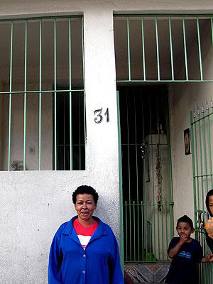 A diarista Maria das Graças da Silva posa em frente à casa que pode perder para o alargamento da Avenida itaquera (Foto: Raphael Prado/G1)