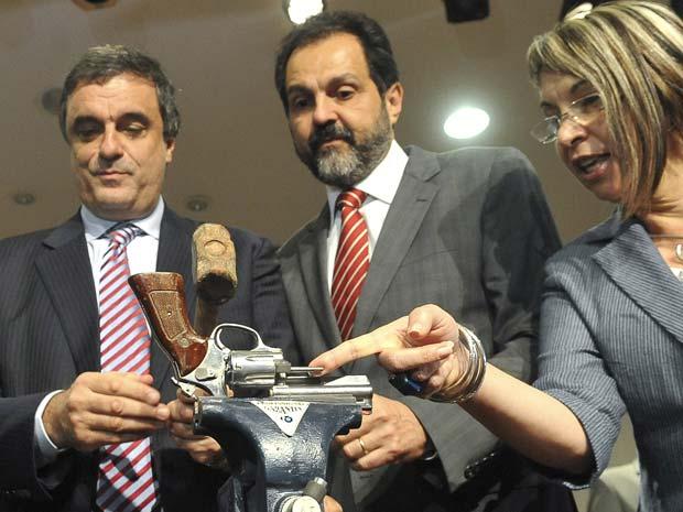 O ministro da Justiça, José Eduardo Cardozo, o governador do DF, Agnelo Queiroz (centro), e a secretária de Entorno de Goiás, Regina Miki, com arma apreendida (Foto: Elza Fiúza/Abr)