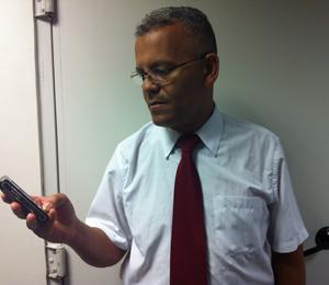 Luiz Cláudio dos Santos, de 52 anos, e seu celular de dois chips. (Foto: Amanda Demetrio/G1)