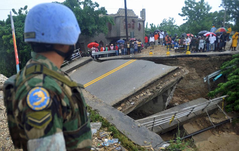 25 de outubro - Pessoas ficam ilhadas em bairro de Porto Príncipe depois de uma ponte ser destruída pela passagem do furacão Sandy pelo Haiti.