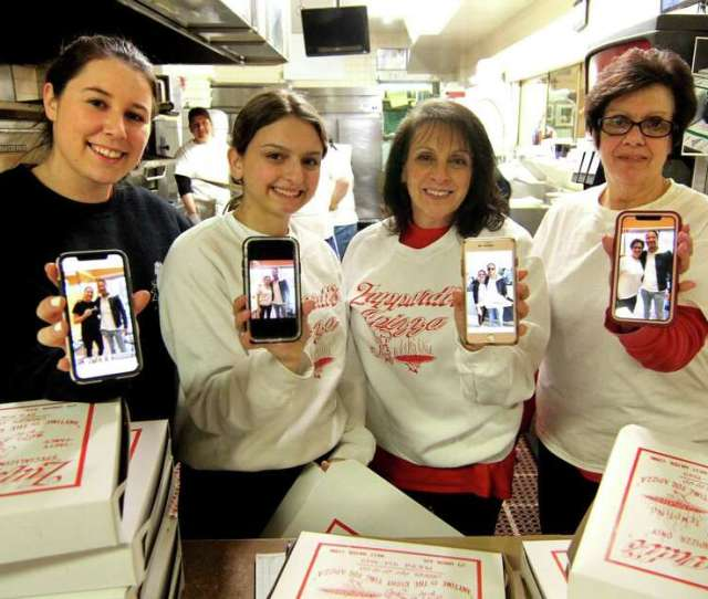 Some Of The Staff Of Zuppardis Apizza Hold Up Their Phones With Photos Of Davind Portnoy