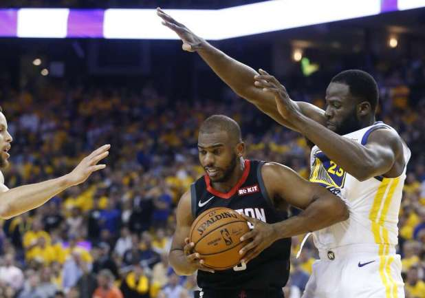 Chris Paul (3), guard of the Houston Rockets, is surrounded by Stephen Curry, escort of the Golden State Warriors, on the left, and Draymond Green (23) during the first half of Game 5 of the semifinals of the Western Conference of the NBA at the Oracle Arena on Wednesday, May 8, 2019., in Oakland. Photo: Elizabeth Conley / Staff photographer