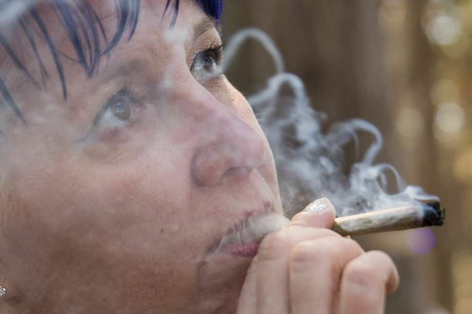 Carrie Bassett of Phoenix, Arizona smokes a marijuana joint in the consumption area of Grass Lands at Outside Lands in Golden Gate Park in San Francisco, Calif. on August 9, 2019. Photo: Douglas Zimmerman/SFGate.com