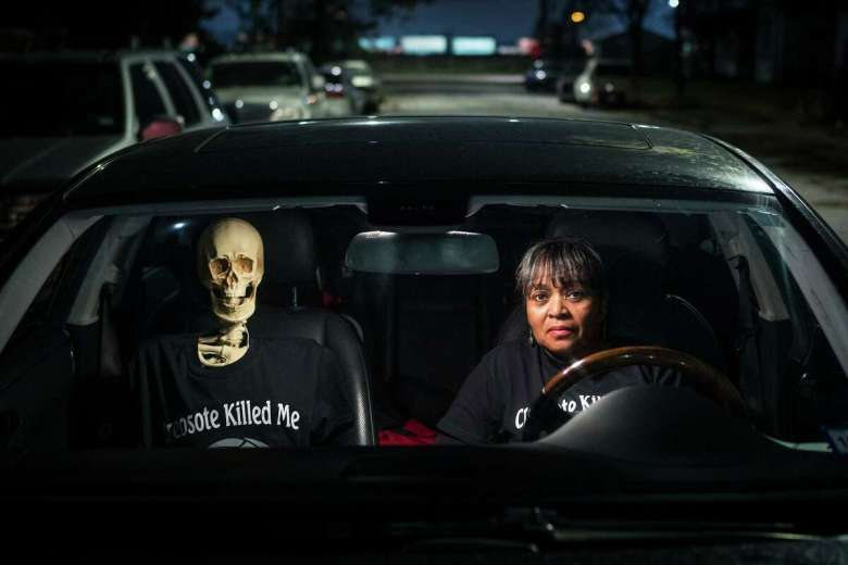 Leisa Glenn sits in her car with a skeleton her group has dubbed