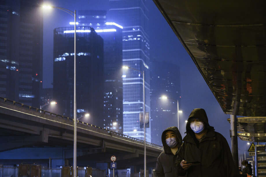 Men wear protective masks and check their phones while waiting for the bus on a nearly empty street on Feb. 7, 2020 in Beijing. The new coronavirus identified in China has spread rapidly since its emergence at the beginning of 2020. Read through to follow the progress of the outbreak response. Photo: Kevin Frayer, Getty / 2020 Getty Images