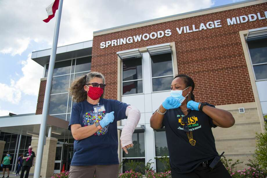 """Lori Douglass, a fifth-grade teacher at Northgate Crossing Elementary School in Spring ISD, left, does an """"air elbow"""" with Nichole Bowman as they prepare to distribute Chromebooks to students for remote learning April 27 at Springwoods Village Middle School in Spring. Photo: Brett Coomer/Staff Photographer / ? 2020 Houston Chronicle"""