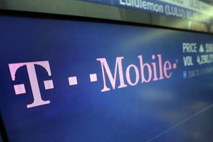 In this Feb. 14, 2018, photo, the logo for T-Mobile appears on a screen at the Nasdaq MarketSite in New York. T-Mobile, one of the three largest mobile carriers in the U.S., suffered a widespread network outage on Monday, June 15, 2020.