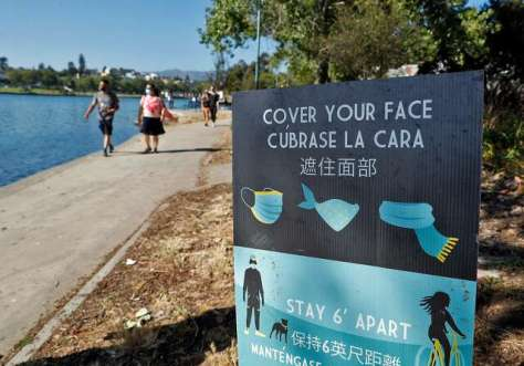 Signs encourage wearing a mask at Lake Merritt in Oakland in June.