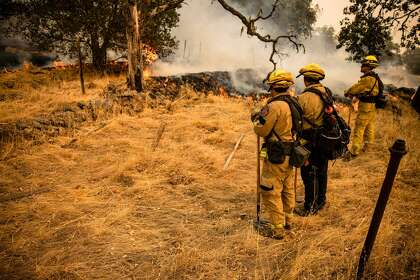 Fire Fighters watch as the edge of the fire creeps across a field towards a fire line they scrapped into the earth with hand tools as the Glass Fire continues to burn in Napa Valley, California on September 29, 2020. - Two California wildfires that ravaged Napa's famous wine region and killed three people exploded in size Tuesday as firefighters faced a weeks-long battle to contain the blazes. The wildfire remains at 0% containment since it began three days ago and now threatens more than 10,000 structures.