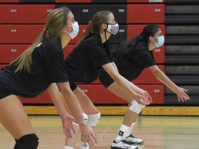 Volleyball players adapting to game wearing masks