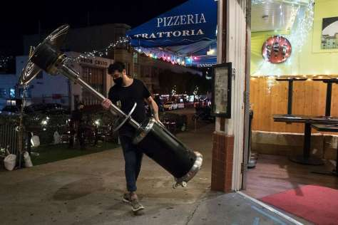 Elias Gambaccini brings in a propane heater as he shuts down his restaurant's outdoor seating at Pizzeria Trattoria in North Beach in San Francisco. Across California, some counties will begin allowing some business activities to resume, including outdoor dining, after Gov. Gavin Newsom rescinded regional stay-home orders.