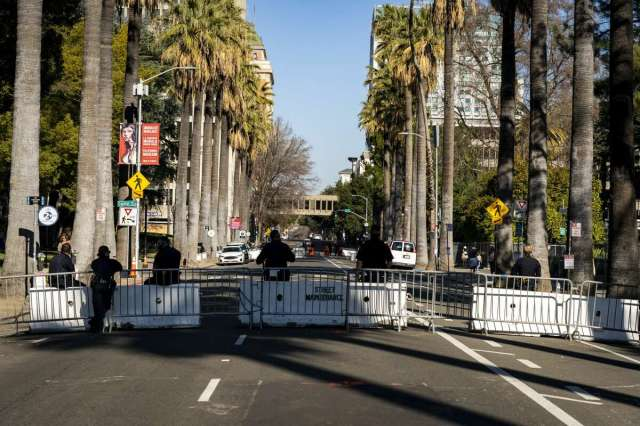 Sacramento police officers stand guard securing the perimeter of the California Capitol in Sacramento, Calif. on Sunday, Jan. 17, 2021Â