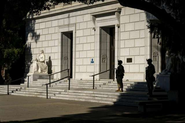 Two National Guards stand guard on the steps of a government building across from the California Capitol in Sacramento, Calif. on Sunday, Jan. 17, 2021