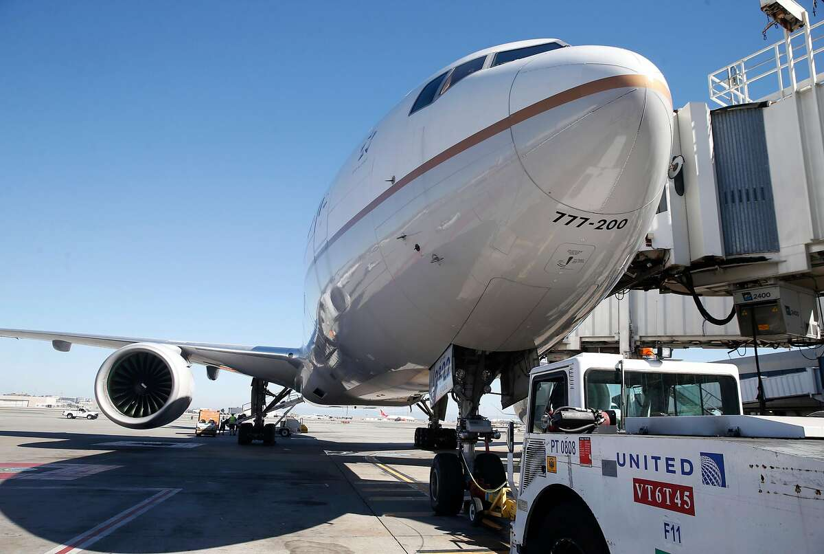 A United Airlines Boeing 777 is readied for departure to Honolulu from gate F11 at SFO in San Francisco, Calif. on Thursday, Oct. 15, 2020. As the airline industry sees a modest rise in travel, a rapid COVID-19 testing site has been set up at the airport to provide travelers with documentation of test results to present upon arrival at their final destinations.