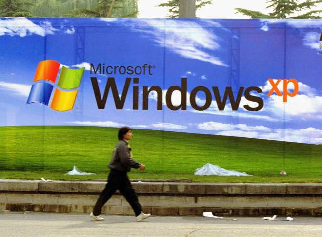 A man walks past a Microsoft billboard featuring its latest software, Windows XP, at the entrance of a conference center November 7, 2001 in Beijing.