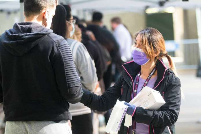 My Lo hands out protective masks to people outside Zuckerberg San Francisco General Hospital waiting to receive the COVID-19 vaccine in San Francisco on April 15, 2021. It was the first day that anyone over 16 years old in California could receive the COVID-19 vaccine.